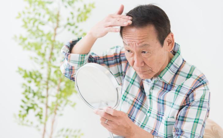 鏡で髪の毛を見る男性
