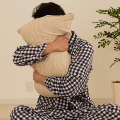 枕を抱きしめる男性